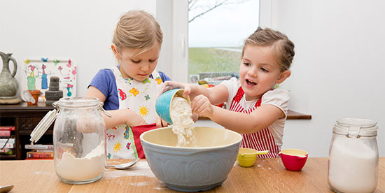 Due bambine all'opera in cucina